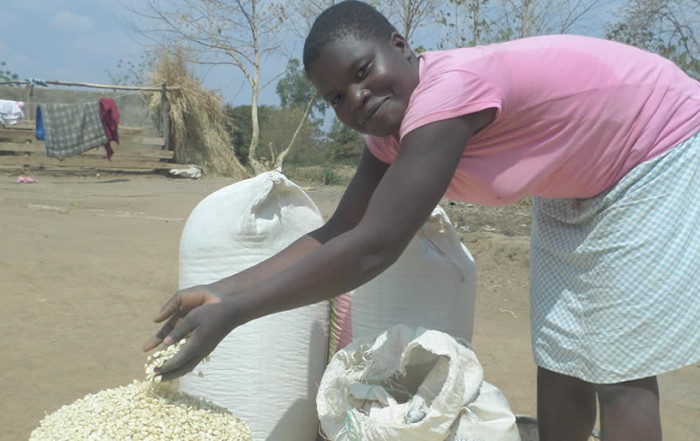 Tiyamike Showing her Maize Harvest in Malawi