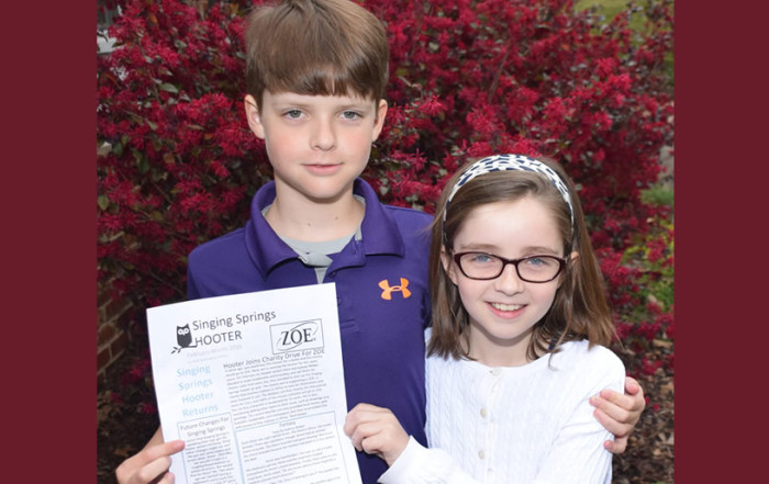 Children holding ZOE newspaper