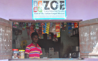 Boy in shop with ZOE sign